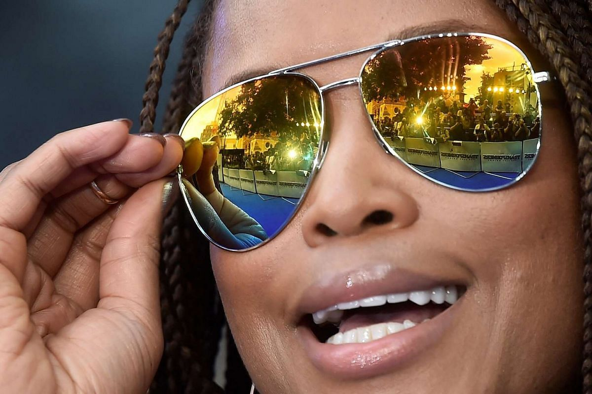 Photographers are reflected in the sunglasses of Eve Cooper as she arrives for the world premiere of Transformers: The Last Knight, at a cinema in central London, Britain, June 18, 2017.