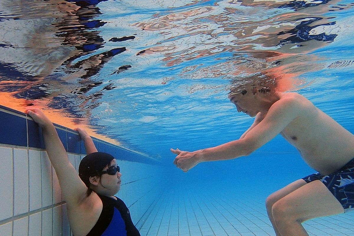 """Mr Tay encourages his daughter, as she holds her breath underwater at Hougang Swimming Complex. They go swimming at least once a month as he believes that sports activities are good for Ms Tay's health and overall well-being. He adds: """"We cannot make"""