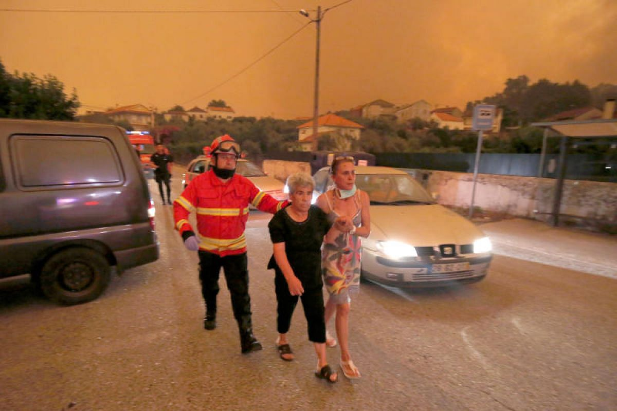Local residents being evacuated during a forest fire from the village of Derreada Cimeira in Portugal on Sunday (June 18).