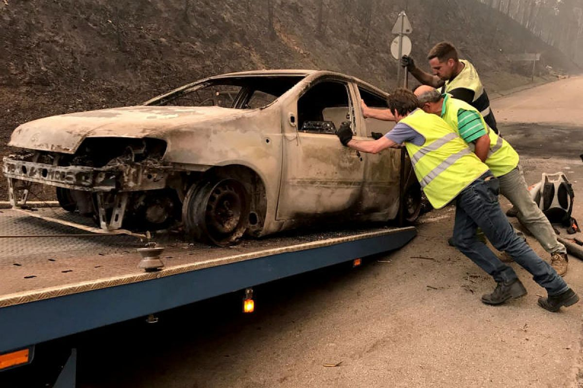 A burnt car being moved onto a tow truck during a forest fire near Pedrogao Grande in Portugal on Sunday (June 18).