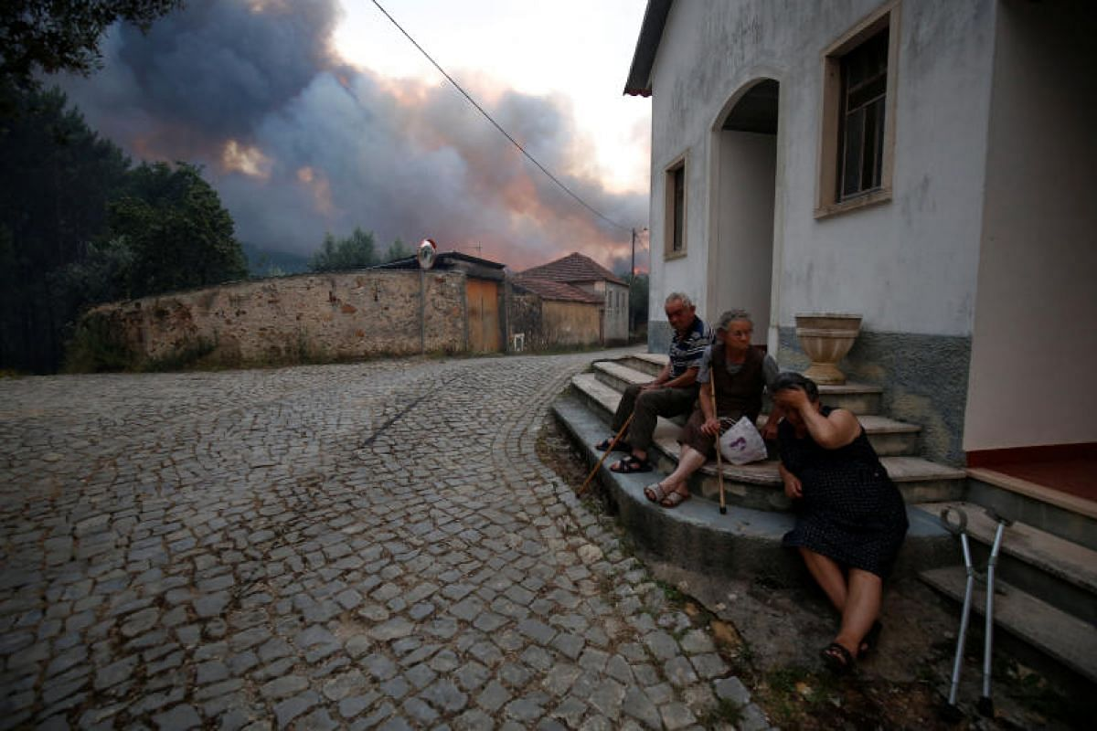 Villagers sitting outdoors as a forest fire burns near the village of Fato in central Portugal on Sunday (June 18).