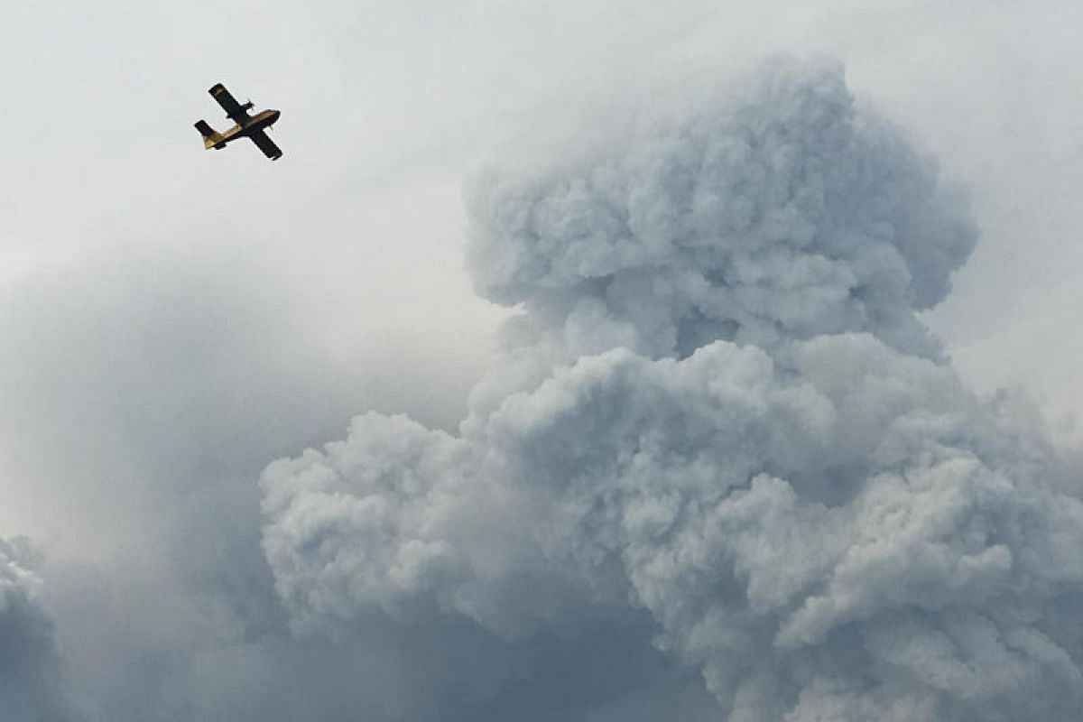 A fire-fighting plane passing through smoke as it pulls up from the Zezere River after picking up water to put out forest fires in the area near Pedrogao Grande on Sunday (June 18).