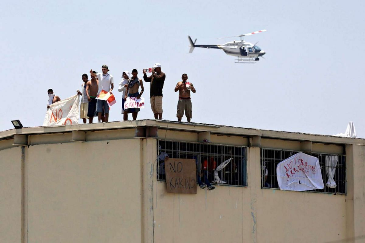 Inmates stand on the roof of the Topo Chico prison as a helicopter flies over the area during a massive riot after dozens of prisoners were transferred to other prisons, according to local media, in Monterrey, Mexico, June 19, 2017.