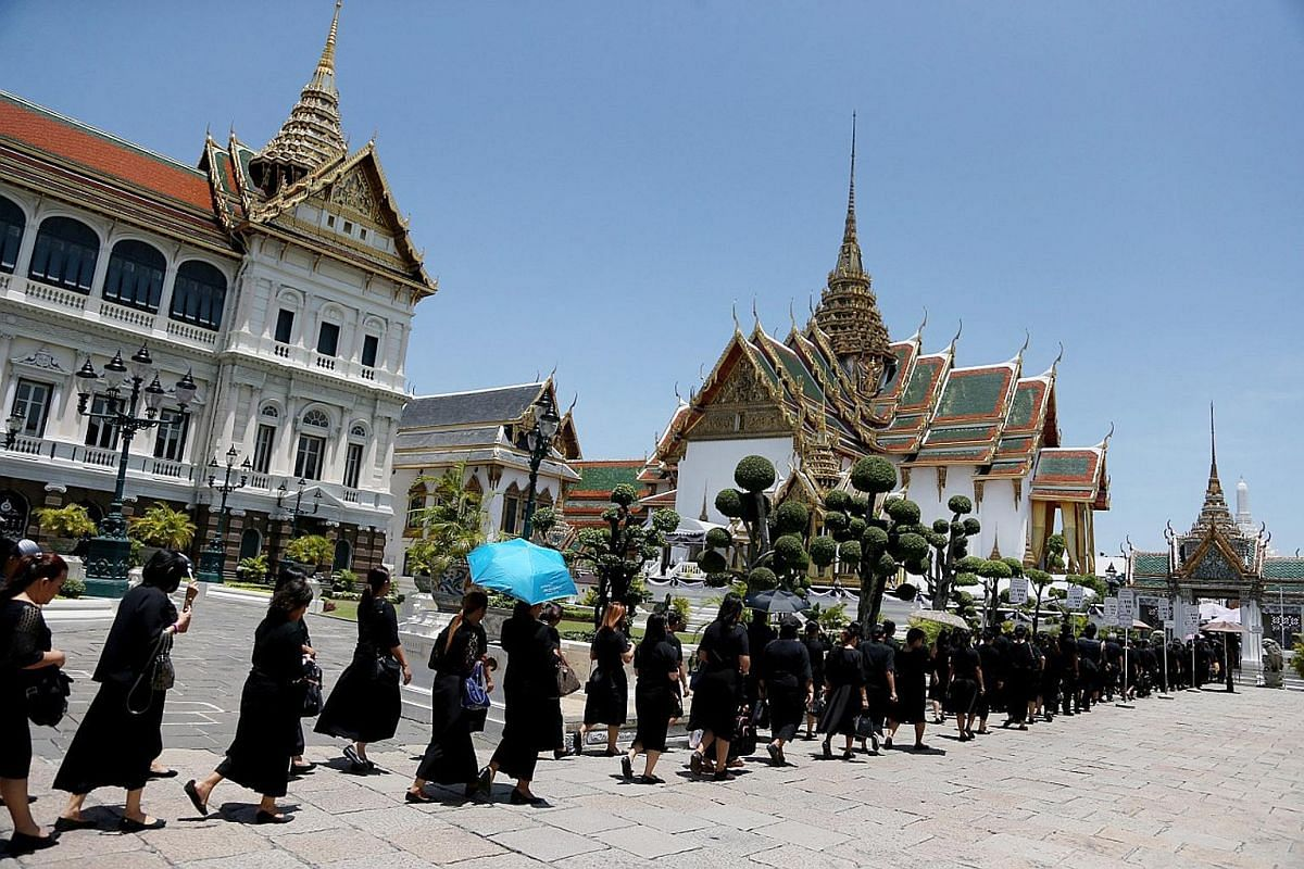 Thais holding portraits of King Bhumibol Adulyadej as they line up to pay their last respects at the Grand Palace in Bangkok last October. There will be 200 sculptures, including those of 40 gods, 20 garuda and over a hundred animals, that will be po