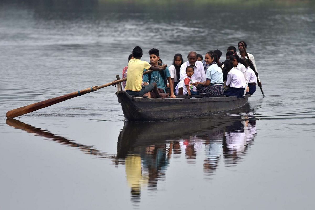 Indian children join commuters as they travel to school on a boat across floodwaters in Rajbari village on the outskirts of Guwahati in Assam state on June 20, 2017.