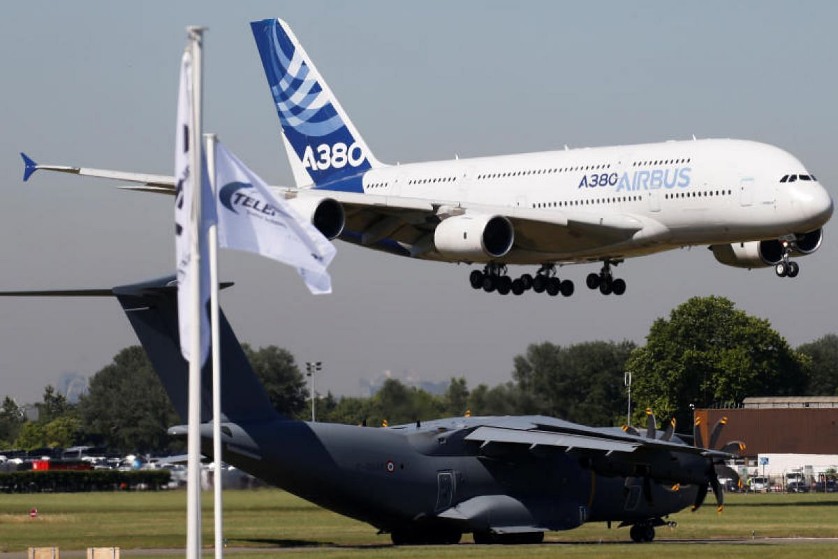 An Airbus A-380 taking flight over an Airbus A-400M during an air display. French President Emmanuel Macron flew in on the Airbus A-400M military transporter to launch the aviation showcase.