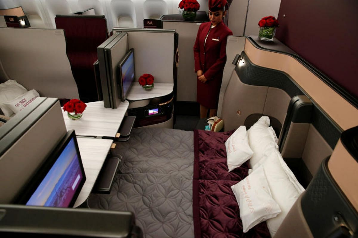 A Qatar Airways crew member offering air show visitors a sneak peek at the business class seats of an Boeing 777 aircraft. The seats, dubbed Qsuite, feature the industry's first double bed in business class, with privacy panels that allow passenger