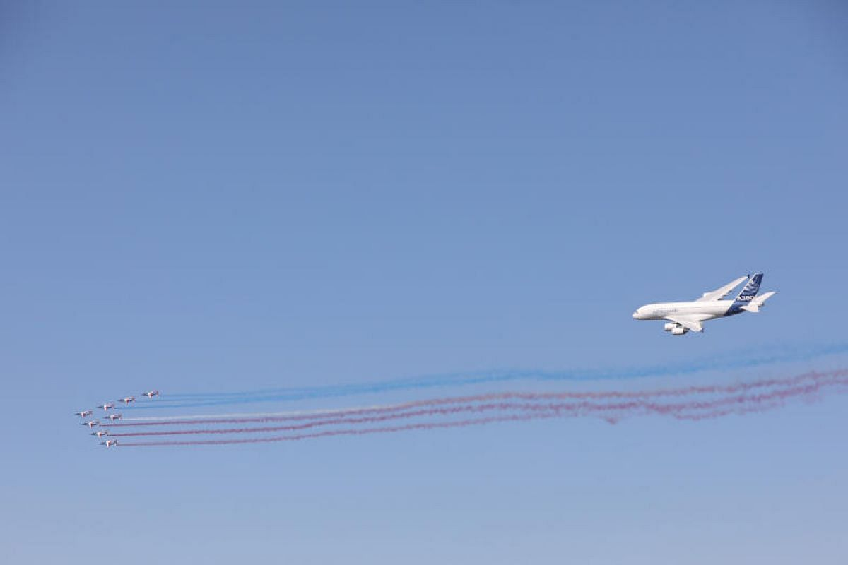 Patrouille de France jets emitting red, white and blue contrails during an aerobatic flying display while an Airbus SE A-380 follows closely on their tail. The event is expected to attract about 200,000 regular visitors, many of whom come especially
