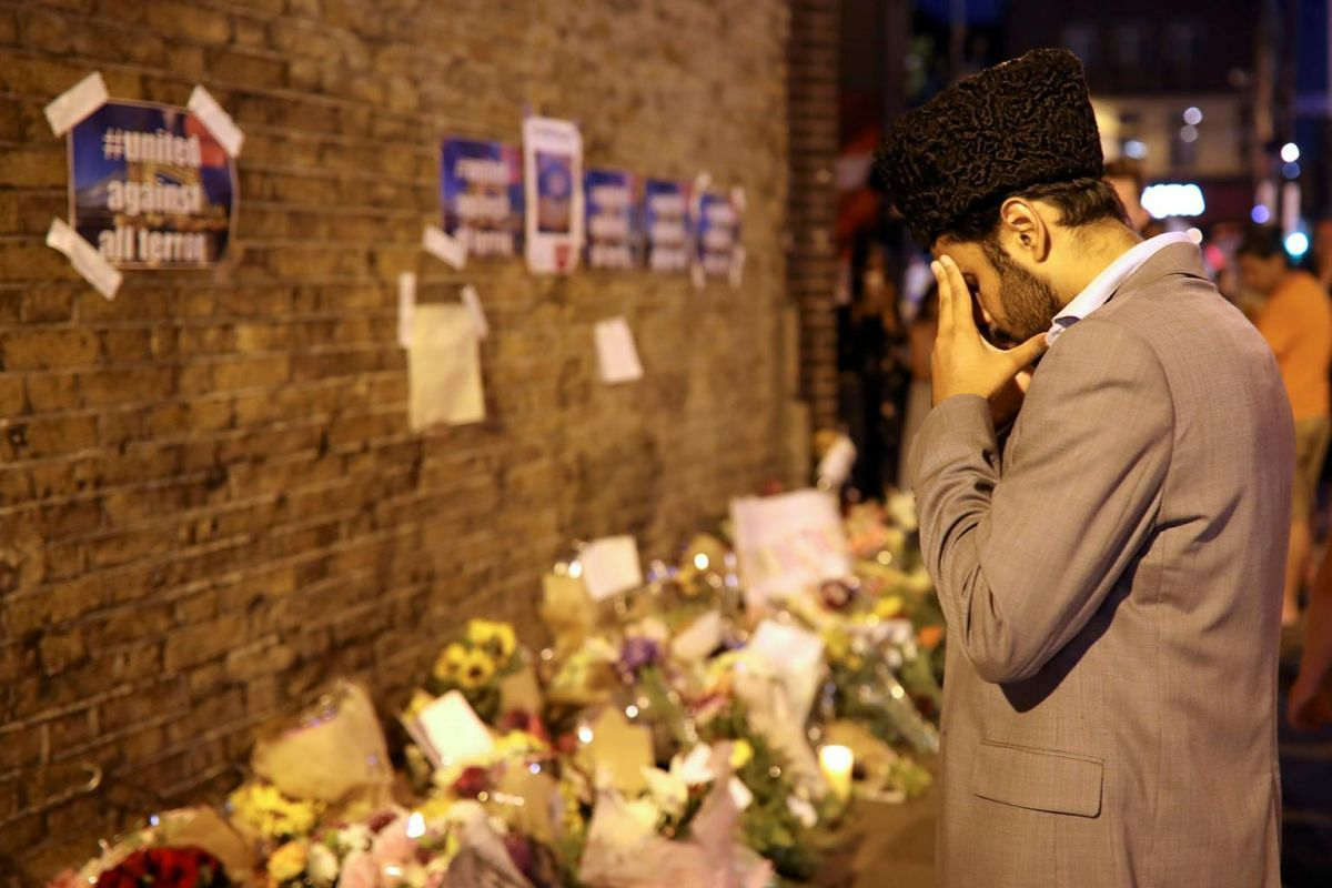 A man prays in front of messages and tributes left near to where a van was driven at Muslims in Finsbury Park, North London.