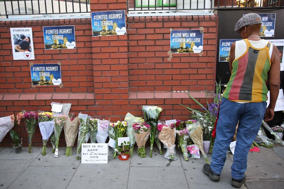 A man looks at floral tributes left close to the scene of a van attack in Finsbury Park.