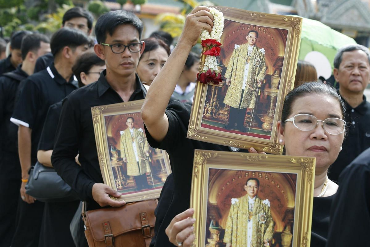 Thais holding portraits of King Bhumibol Adulyadej as they line up to pay their last respects at the Grand Palace in Bangkok last October.