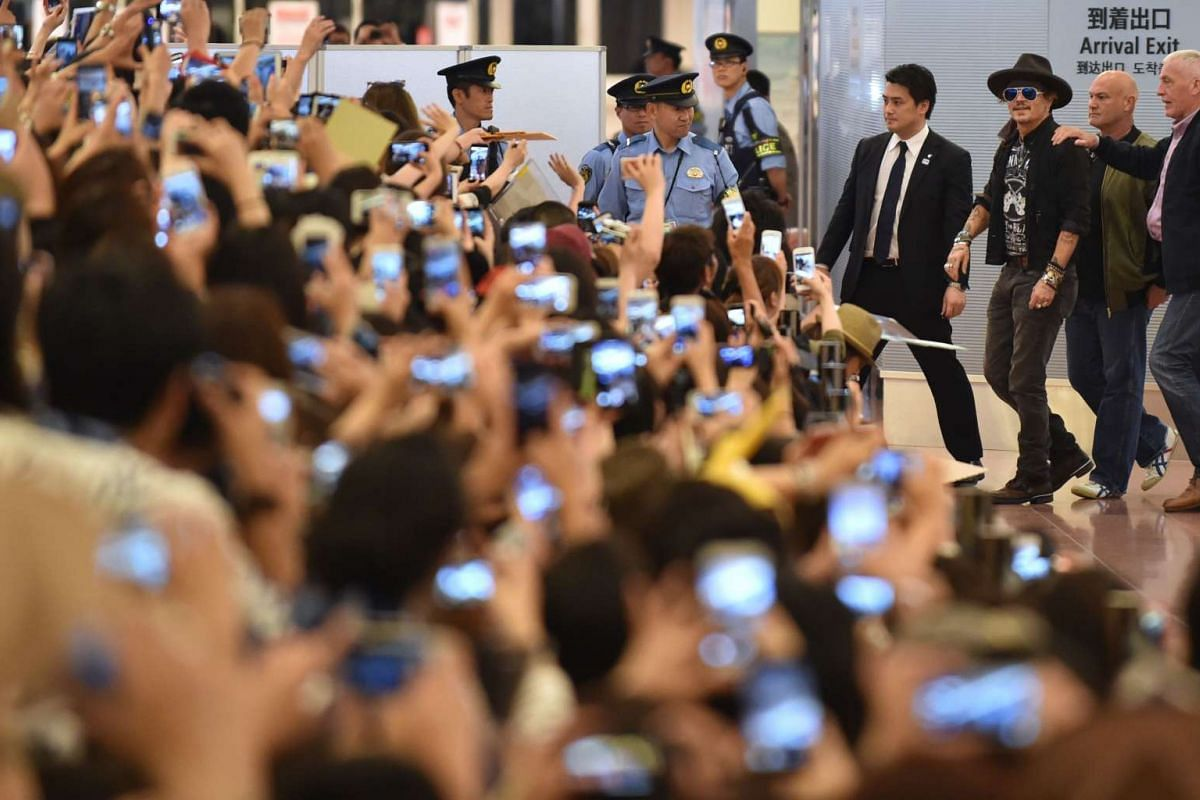 """US actor Johnny Depp (C) is greeted by Japanese fans upon his arrival to take part in promotional events for the Disney movie """"Pirates of the Caribbean: Dead Men Tell No Tales"""" at Tokyo's Haneda Airport in Tokyo on June 20, 2017."""