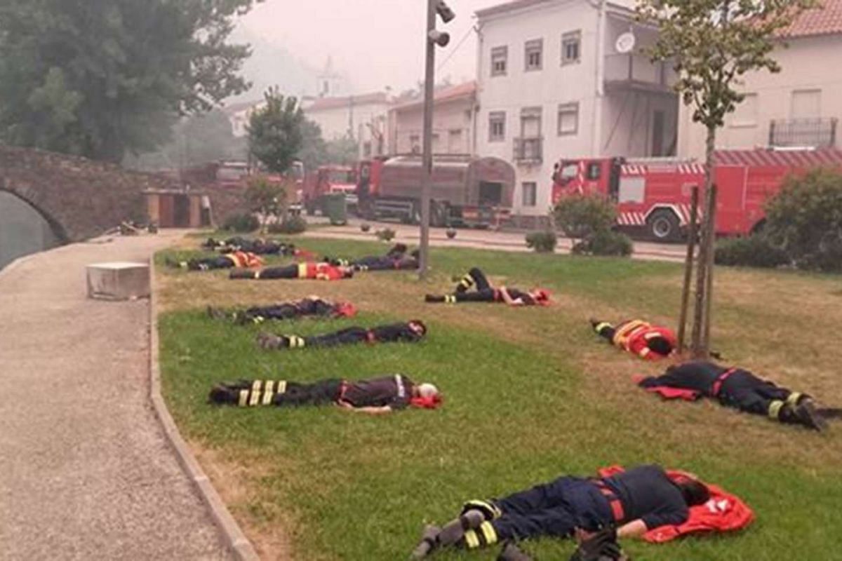 Firefighters rest after fighting wildfires in Alvares, Portugal June 18, 2017, in this picture obtained from social media.