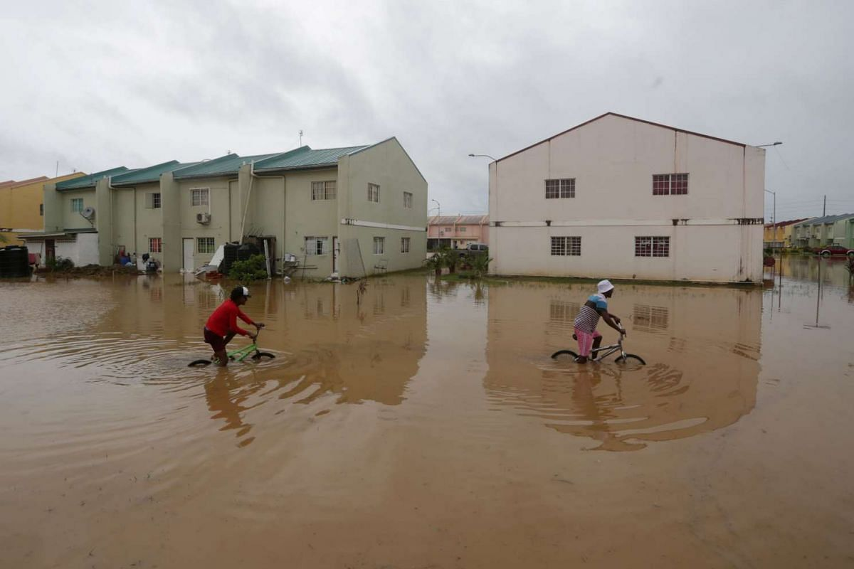 Children ride their bikes through a flooded street in the aftermath of tropical storm Bret, which has since then degenerated into a tropical wave according to the U.S. National Hurricane Center (NHC), in Oropune, Trinidad and Tobago June 20, 2017.