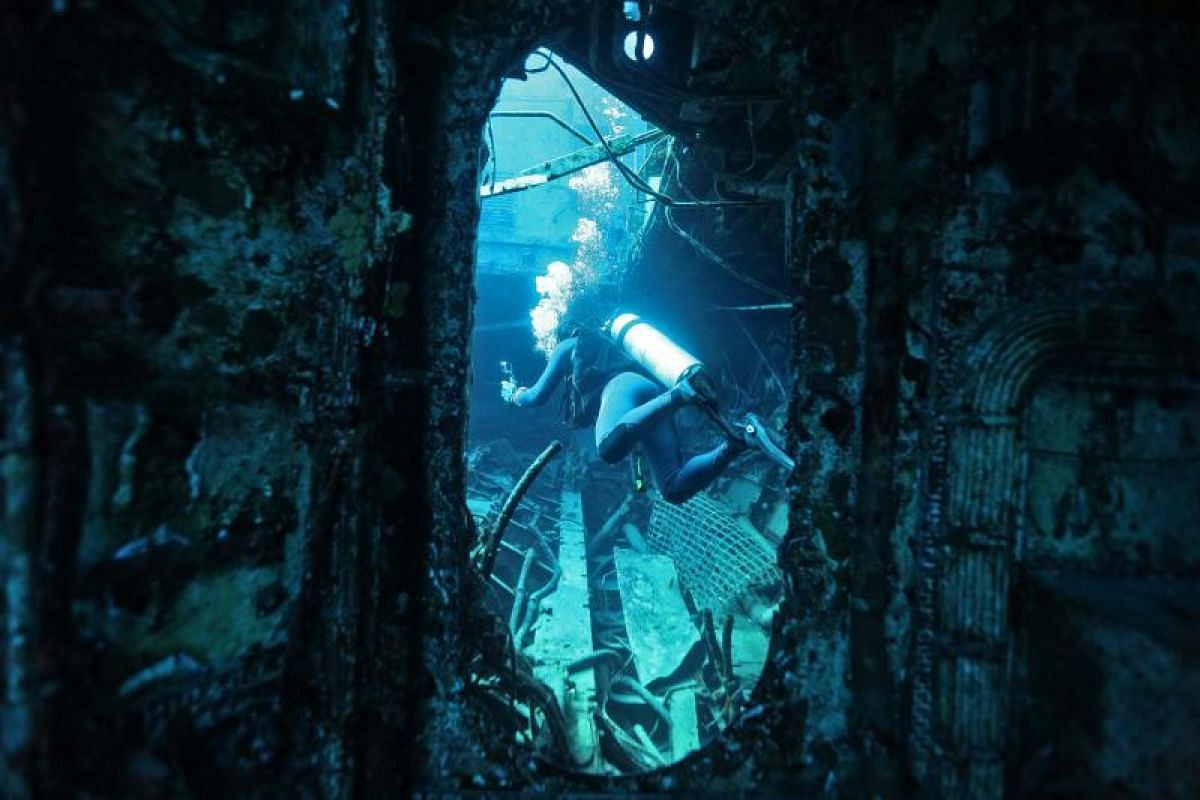 A scuba diver making his way around the wreck of a ship during his dive to monitor coral growth in the Red Sea.