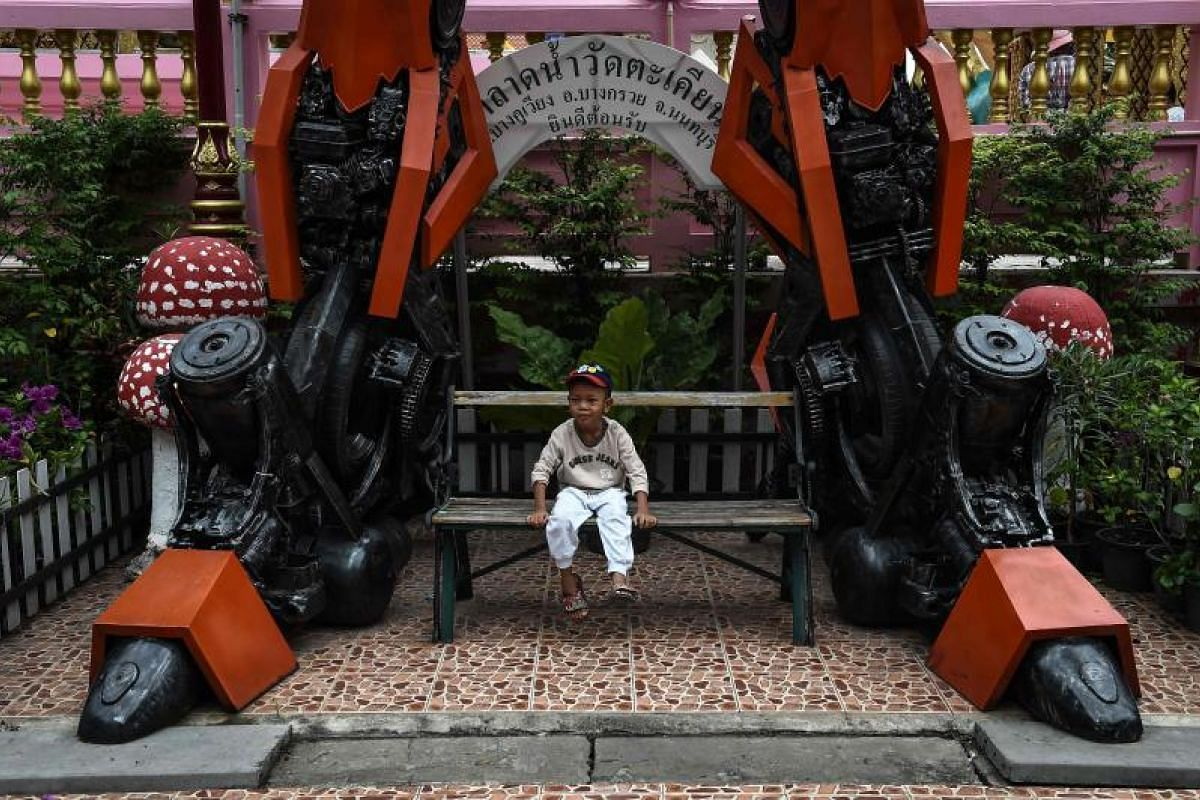 """This boy is probably hoping to """"transform"""" into a superhero, just like the Transformers statue at the Wat Tha Kien Buddhist temple in Nonthaburi."""