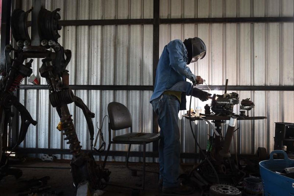 And how are the giant robots made? This is one of the men behind the machines - a metalworker welding pieces at the Ban Hun Lek metalworks shop.