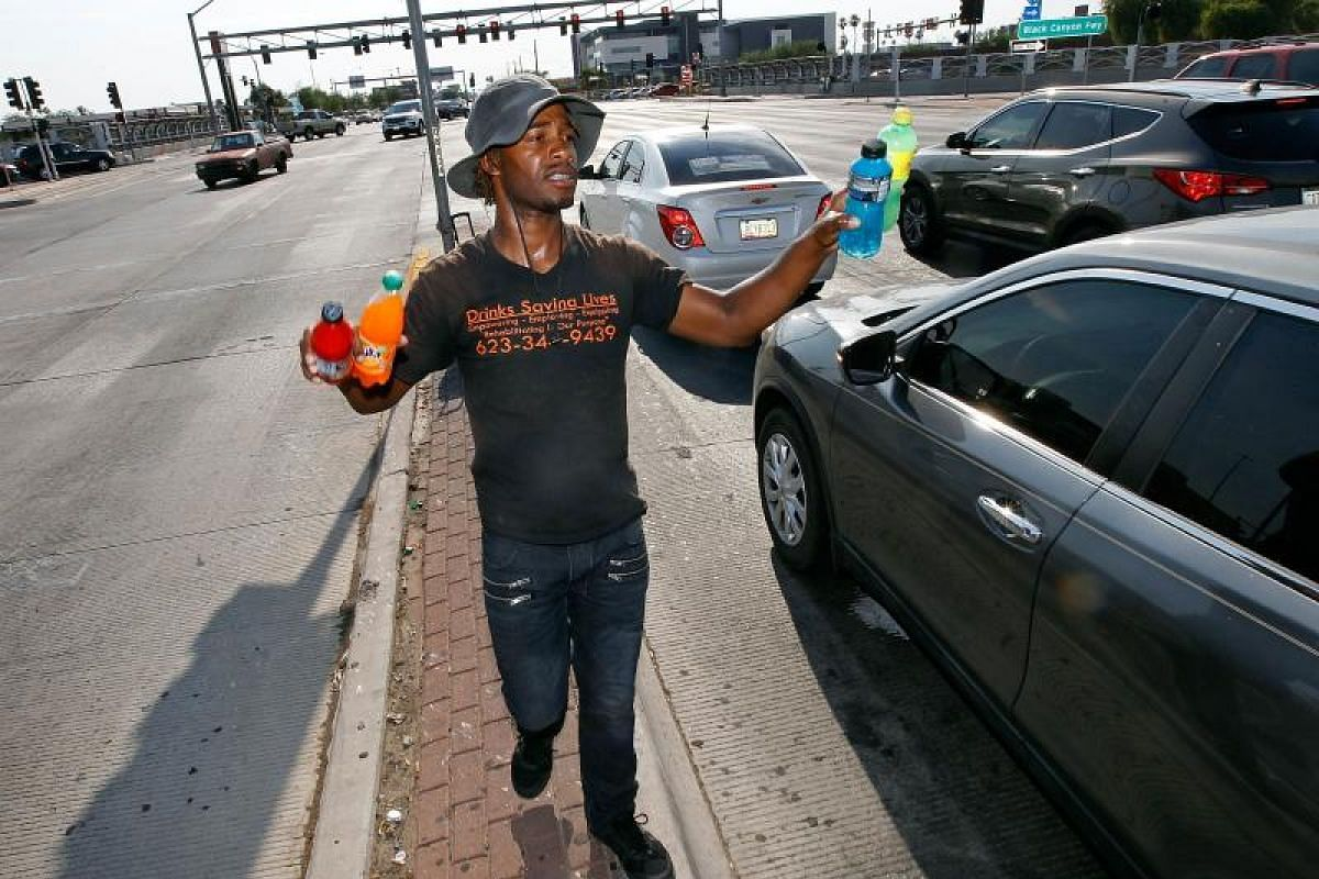 Eric Maurice Clark, 33, selling cold drinks to motorists at a busy intersection in Phoenix, Arizona, on Tuesday (June 20). Record temperatures of nearly 50 deg C were expected on Tuesday for the Phoenix metro area. The heat wave was so severe that it