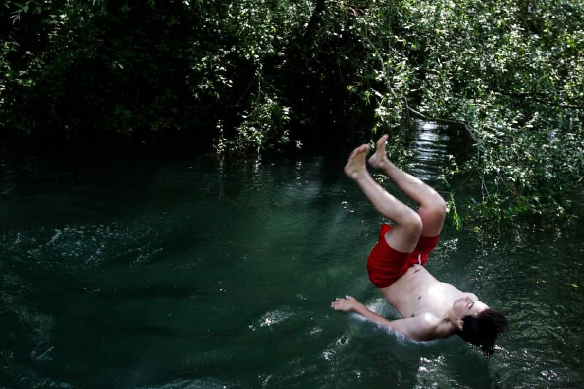 Jumping into the Lis river in Leiria, Portugal is the only answer for some as temperatures go as high as 43 deg C. The country is emerging from three days of national mourning after at least 64 people were killed and more than 150 injured at the week