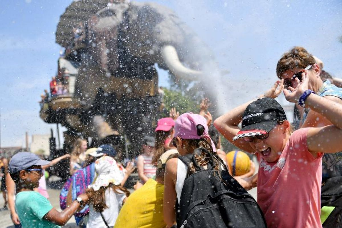 A wood and steel mechanical elephant at the Les Machines de L'Ile, or Machines of the Isle of Nantes, spraying water on children on Tuesday (June 20), in Nantes, western France. The French national meteorological service, Meteo France is forecasting