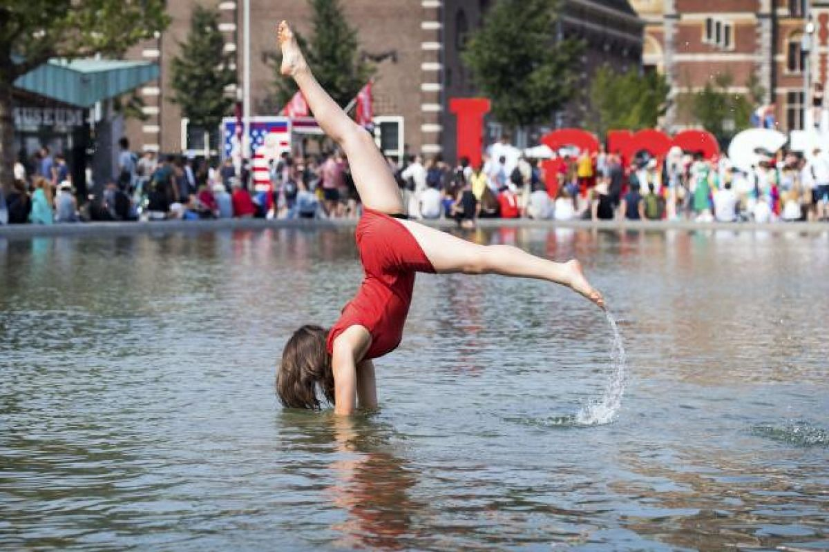 A woman seeking relief from soaring temperatures in Amsterdam at the Museumplein Park on Tuesday (June 20). Many parts of Europe are experiencing higher-than-usual temperatures as a heatwave sweeps across the continent.