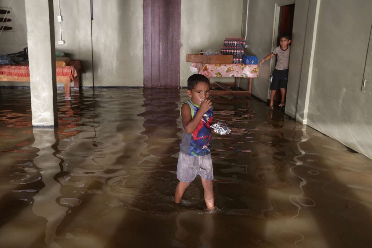 Children walk through their flooded house in Penal, Trinidad and Tobago, June 21, 2017. Tropical Storm Bret, the second of the year and already lowered to the category of tropical wave, caused material damage to houses and infrastructures due to floo