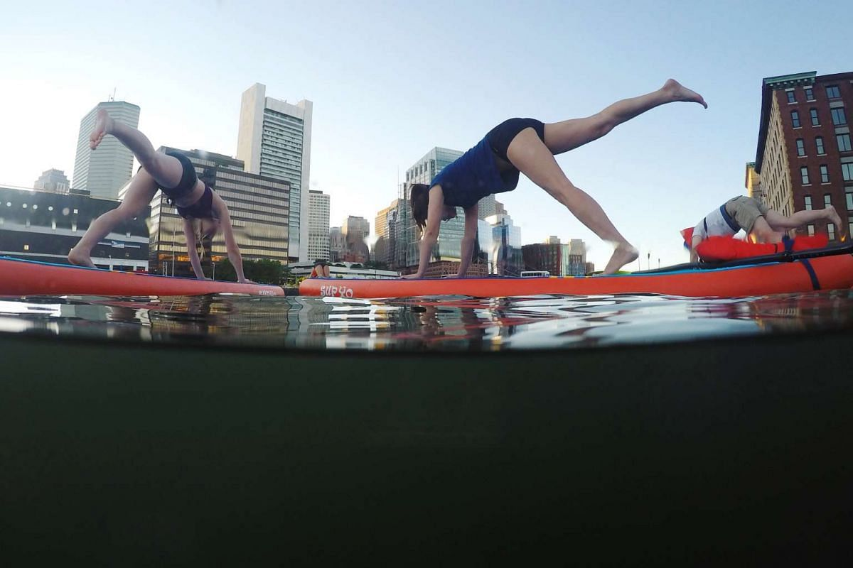 """People take part in a """"Sup Yoga, Boston"""" stand up paddle board yoga class on Fort Point Channel on International Yoga Day in Boston, Massachusetts, U.S., June 21, 2017."""