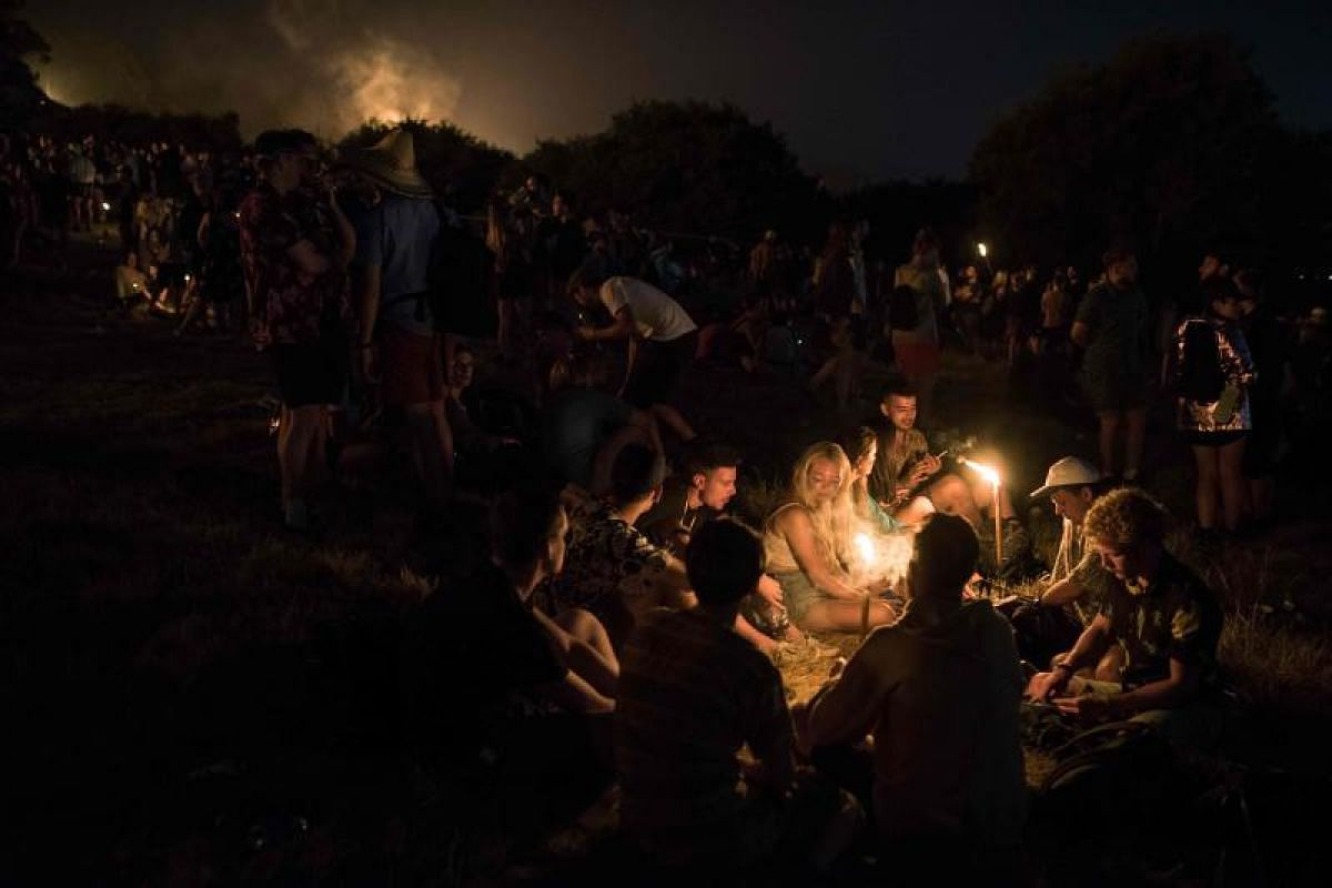 Silent is the night? Not yet, as revellers chat by candlelight after the sun sets on the Glastonbury Festival.