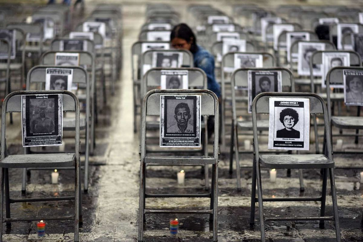 Portraits of victims of forced disappearance hang on empty chairs during the ceremony to commemorate the National Day of the Victims of Enforced Disappearances at Constitution Square in Guatemala City on June 21, 2017.