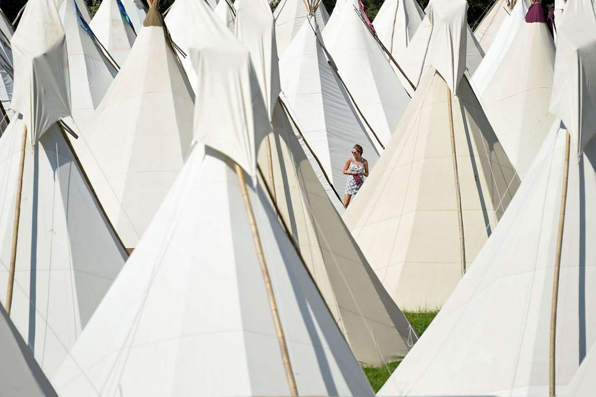 A reveller walks among the tipi tents at the Glastonbury Festival of Music and Performing Arts on Worthy Farm near the village of Pilton in Somerset, South West England, on June 21, 2017