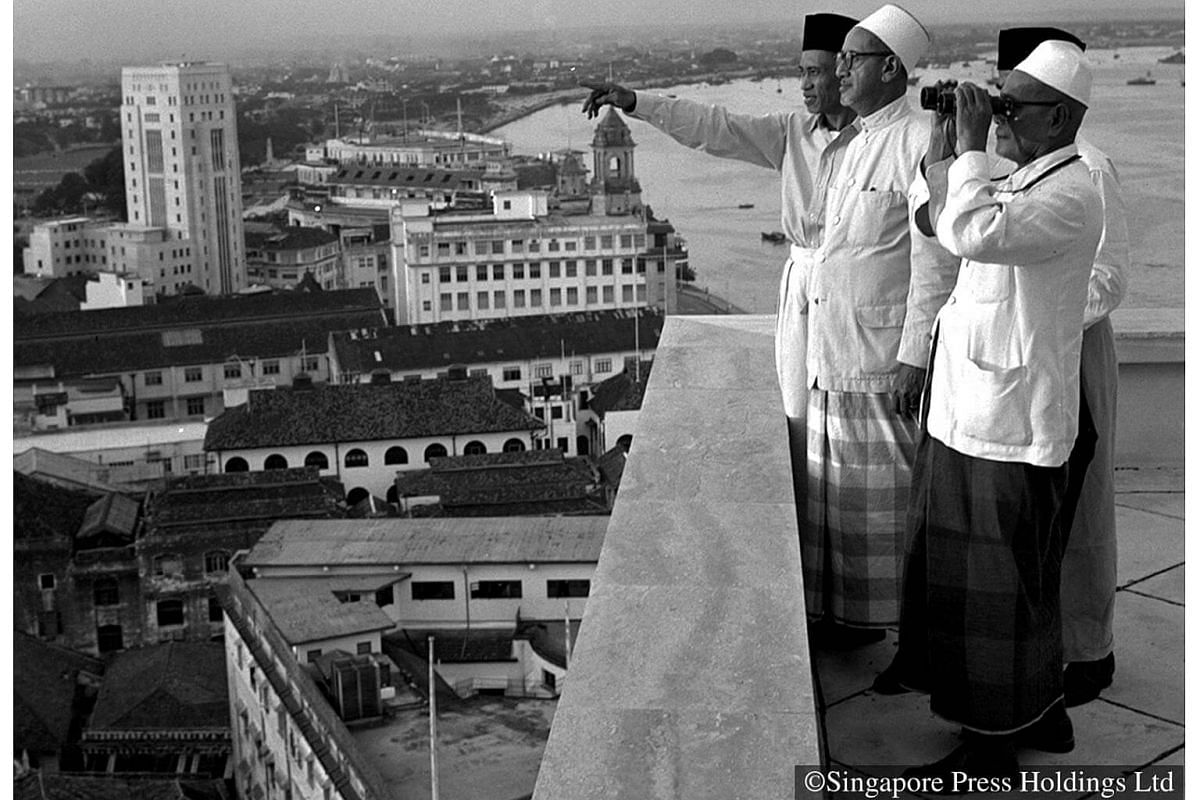 1956: Officials from the Muslim Advisory Board scan the skyline looking for the new moon, the signal for the start of Ramadan, at the rooftop of Asia Building. In Singapore the start of Ramadan is now determined by astronomical calculations rather th