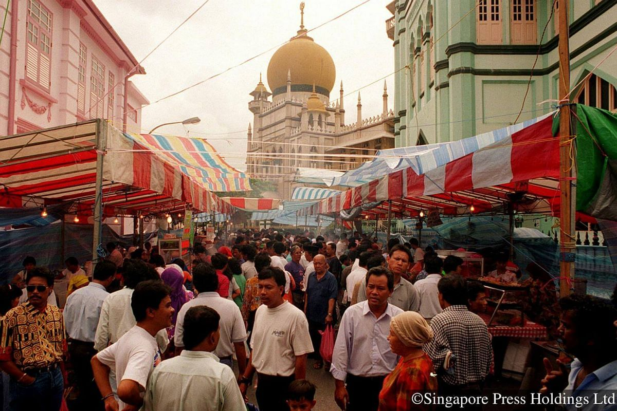 1995: A bustling atmosphere at the bazaar at Bussorah Street, lined with food stalls. The Kampong Glam area remains a favourite with the crowds as they can also do their Hari Raya shopping at the shops nearby.