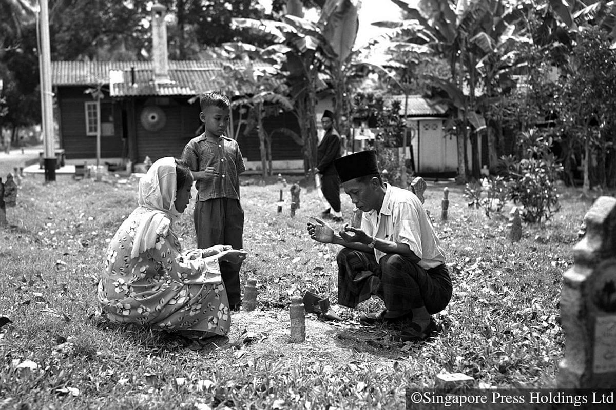 1951: A family visit the grave of a loved one during Hari Raya Puasa. During such visits, prayers are said for the deceased and the grave is cleaned.