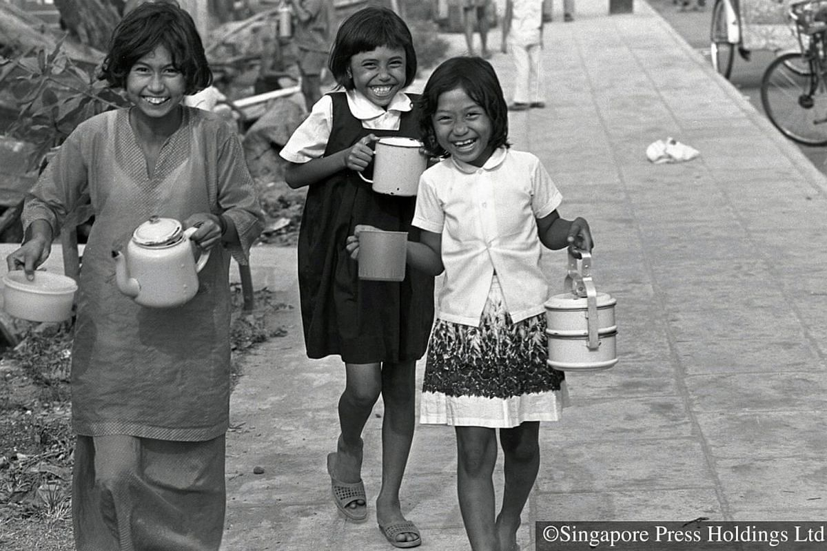 1972: Children carrying bowls and mugs to collect free porridge distributed by the Aminah mosque in Geylang during the fasting month. The porridge is given out by many mosques daily for iftar, or break fast.