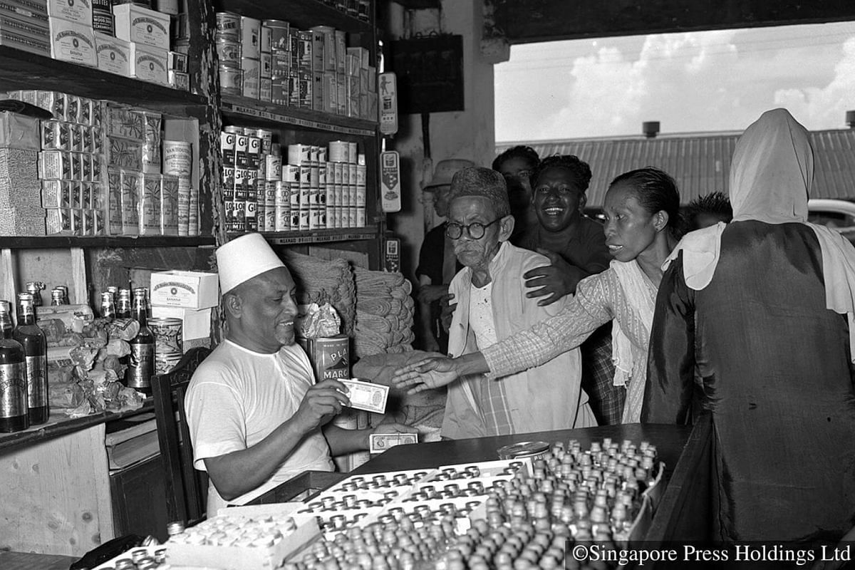 1955: A Muslim shopkeeper in Beach Road handing out money to the poor. During Ramadan, apart from fasting, Muslims are also encouraged to be more charitable towards the needy and perform more good deeds.