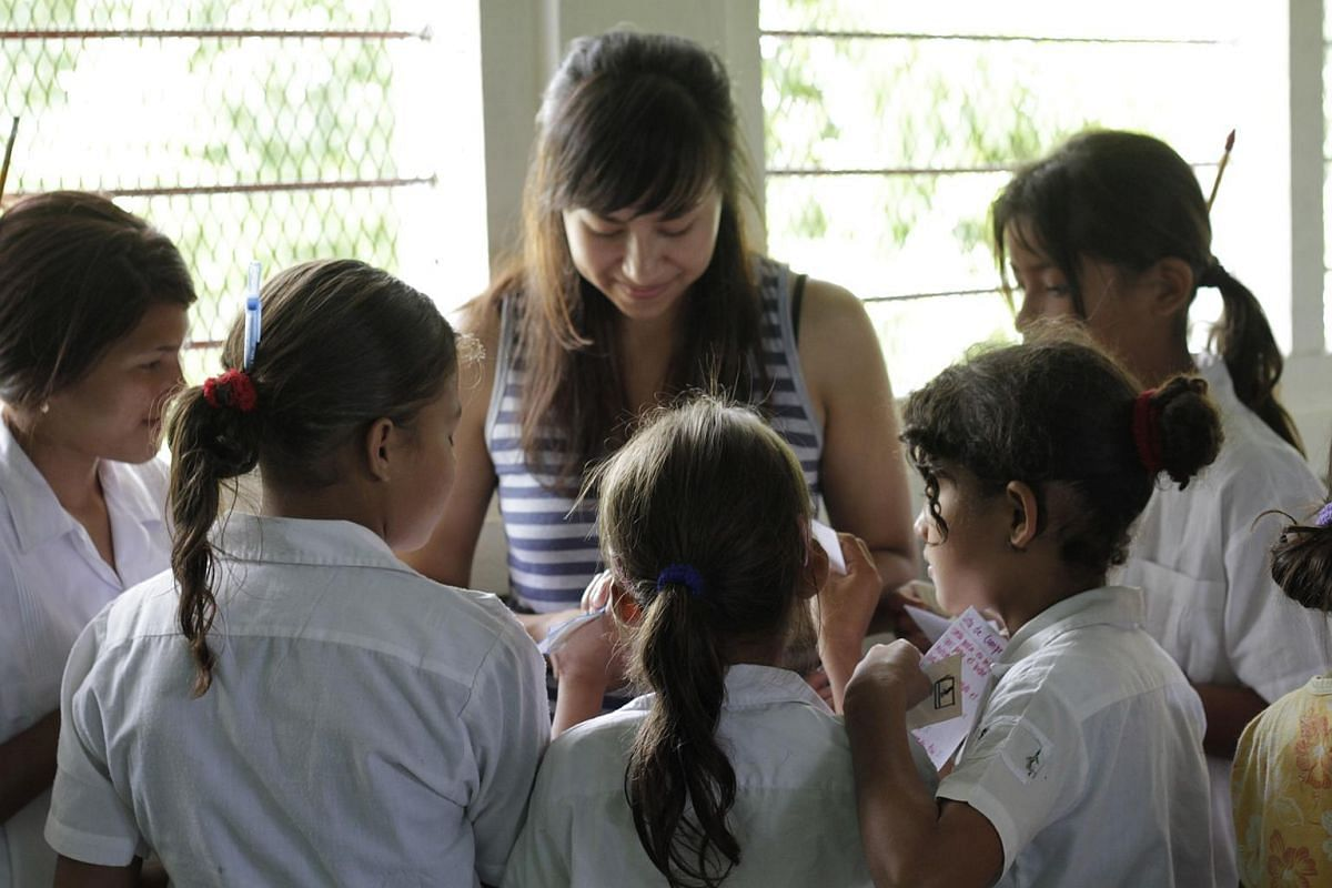 Katia Gómez, founder of Educate2Envision, plays with a group of children in a community in El Paraíso, east of Honduras.