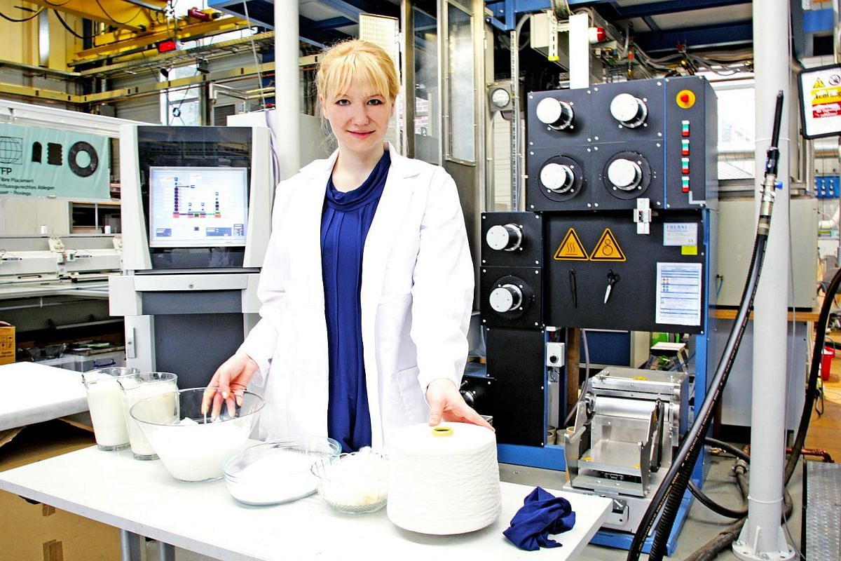 Anke Domaske in her Qmilk laboratory, with a bowl of cloth made from Qmilk fibers, wasted milk, with cloth made from Qmilk fibre.