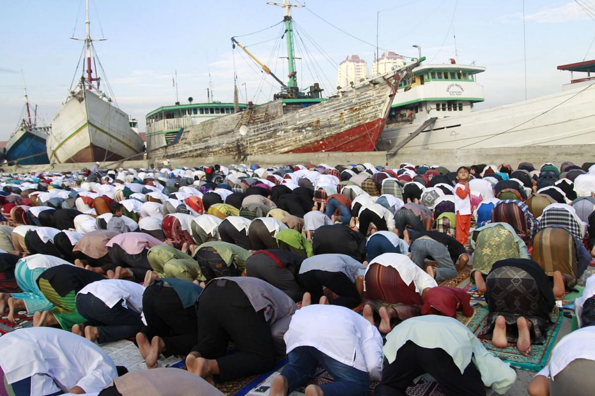 Indonesian Muslims praying near traditional boats during Eid al-Fitr prayers at Sunda Kelapa port in Jakarta, Indonesia, on June 25, 2017.