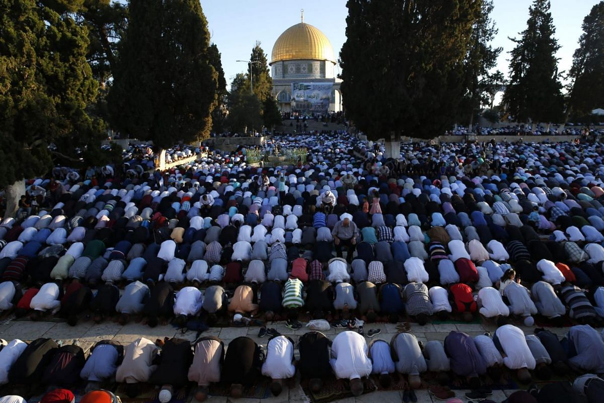 Palestinian Muslims performing the morning Eid al-Fitr prayer near the Dome of Rock at the Al-Aqsa Mosque compound, in the Old City of Jerusalem, on June 25, 2017.