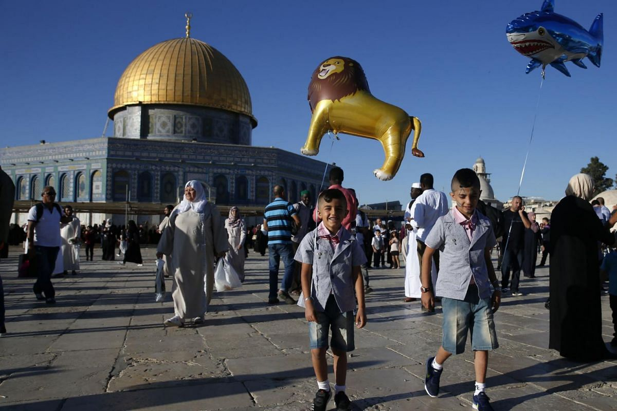 Palestinian boys holding balloons as Muslims gather for the morning Eid al-Fitr prayer near the Dome of Rock at the Al-Aqsa Mosque compound, in the Old City of Jerusalem on June 25, 2017.