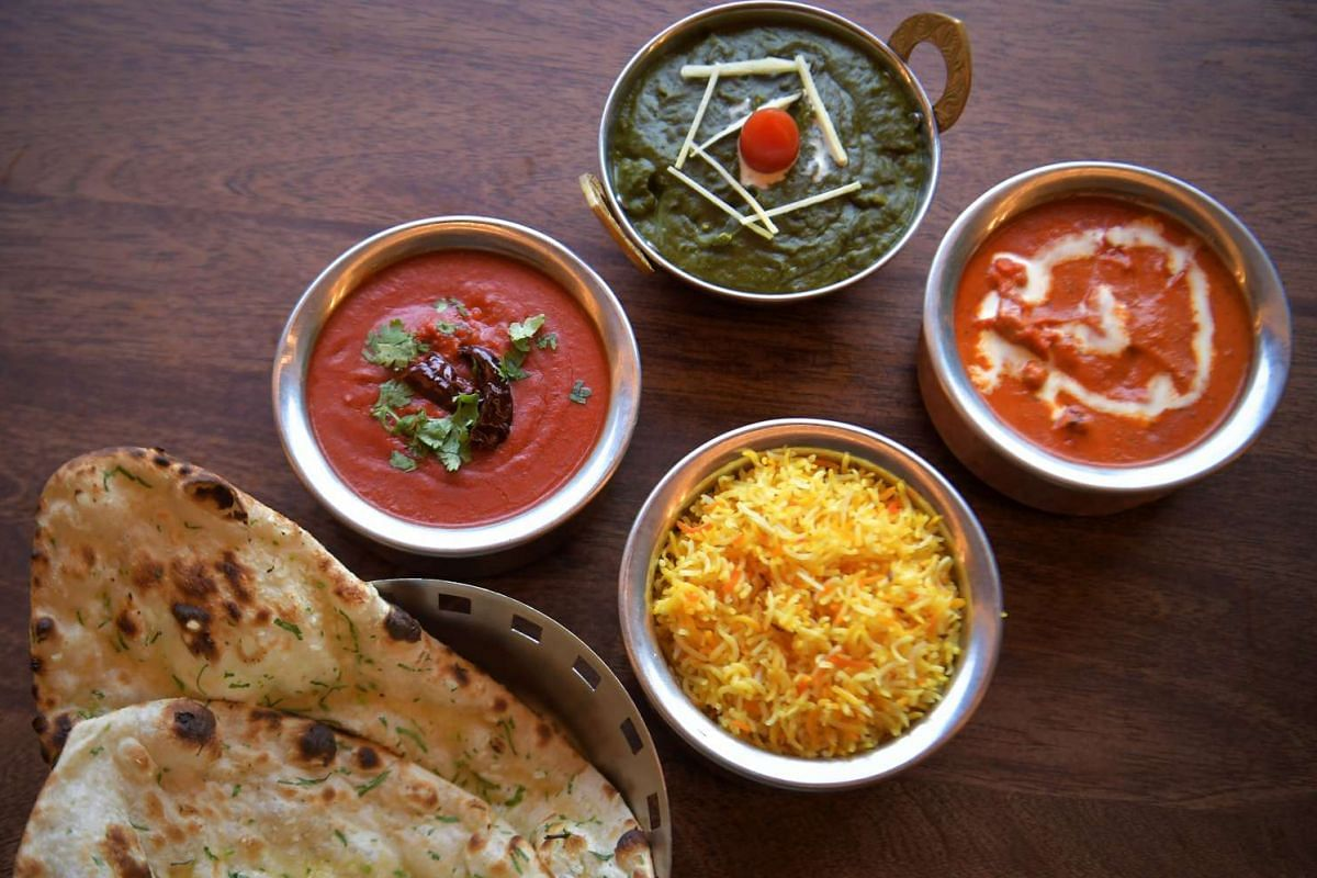 Groovy gravies served in metal pots (above, from left) lamb vindaloo, saag paneer (spinach with cottage cheese) and Dabbawalla butter chicken, with garlic naan and saffron rice.