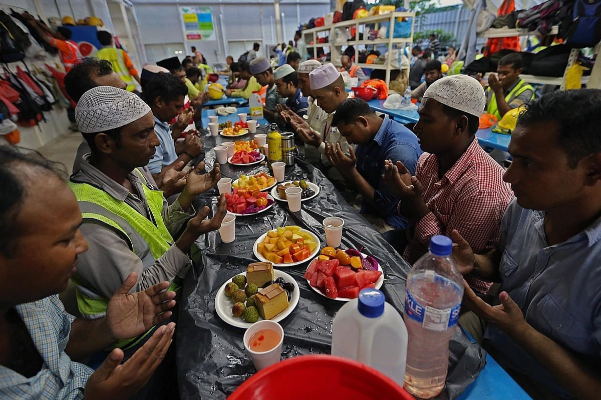 Mr Hossain Md Murad (second from right), 34, praying with other Muslim workers from Bangladesh before they broke fast at the canteen at the Paya Lebar Quarter worksite last week. Mr Hossain, who works as a site supervisor for Lendlease, which is over