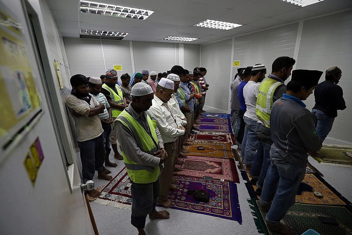 Muslim migrant workers in the prayer room of Paya Lebar Quarter, saying the Maghrib prayer just after sunset. As Muslim workers make up more than 50 per cent of the workforce at Paya Lebar Quarter, Lendlease has provided a prayer room for them. Mr Ri