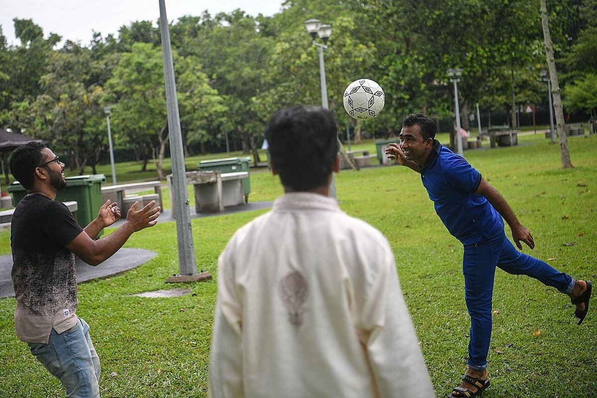 Mr Syedur Rahman Liton (right) playing football with fellow Bangladeshis Mohammad Mashiur Rahman, 32, and Mahbub Hasan Dipu (left), 30, at Pasir Ris Park yesterday on Hari Raya Aidilfitri, which Muslims celebrate to mark the end of fasting.