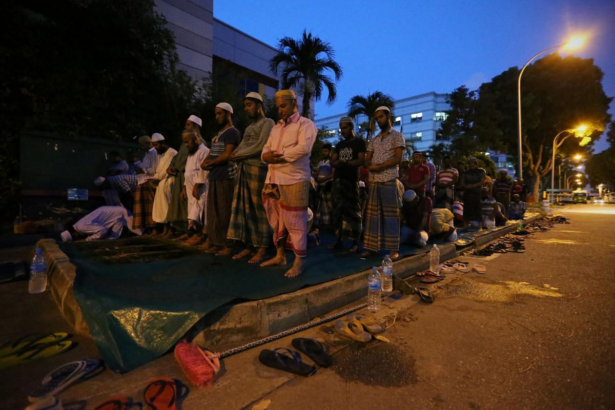 A group of Bangladeshi migrant workers pray by the roadside along Tech Park Crescent outside their dormitories in Tuas.