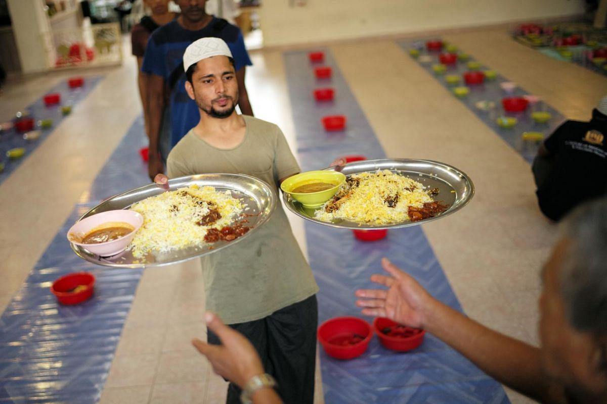 Bangladeshi Mr Almamum Md Sheik, 28, a construction worker for the past 4 years, helps to serve the trays of briyani as Khalid Mosque in Joo Chiat Road prepares for iftar.
