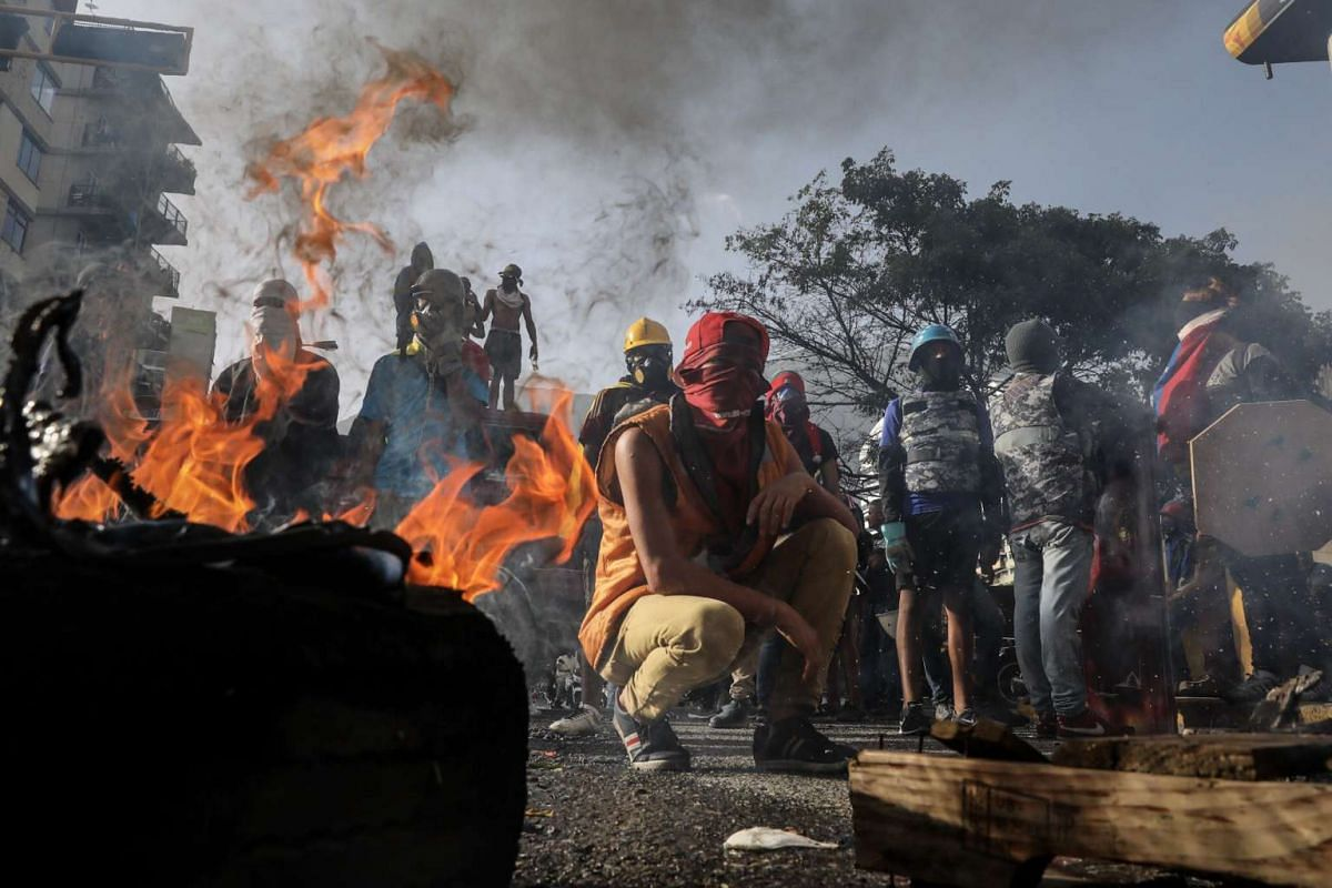 Protesters burn tires and wooden boards to block a road during an anti-government demonstration in Caracas, Venezuela, June 26, 2017. PHOTO: EPA