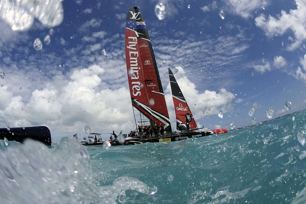 Underwater camera view from water level of Emirates Team New Zealand celebrating after defeating Oracle Team USA during race nine in the Great Sound, Bermuda, June 25, 2017. Emirates Team New Zealand defeated the defender, Oracle Team USA to take hom