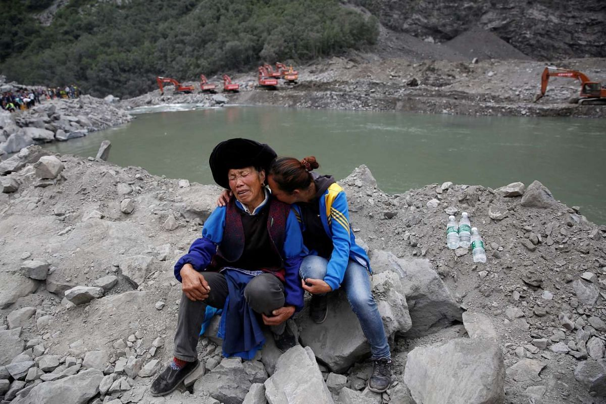 Relatives of victims react at the site of a landslide in the village of Xinmo, Mao County, Sichuan Province, China June 26, 2017. PHOTO: REUTERS