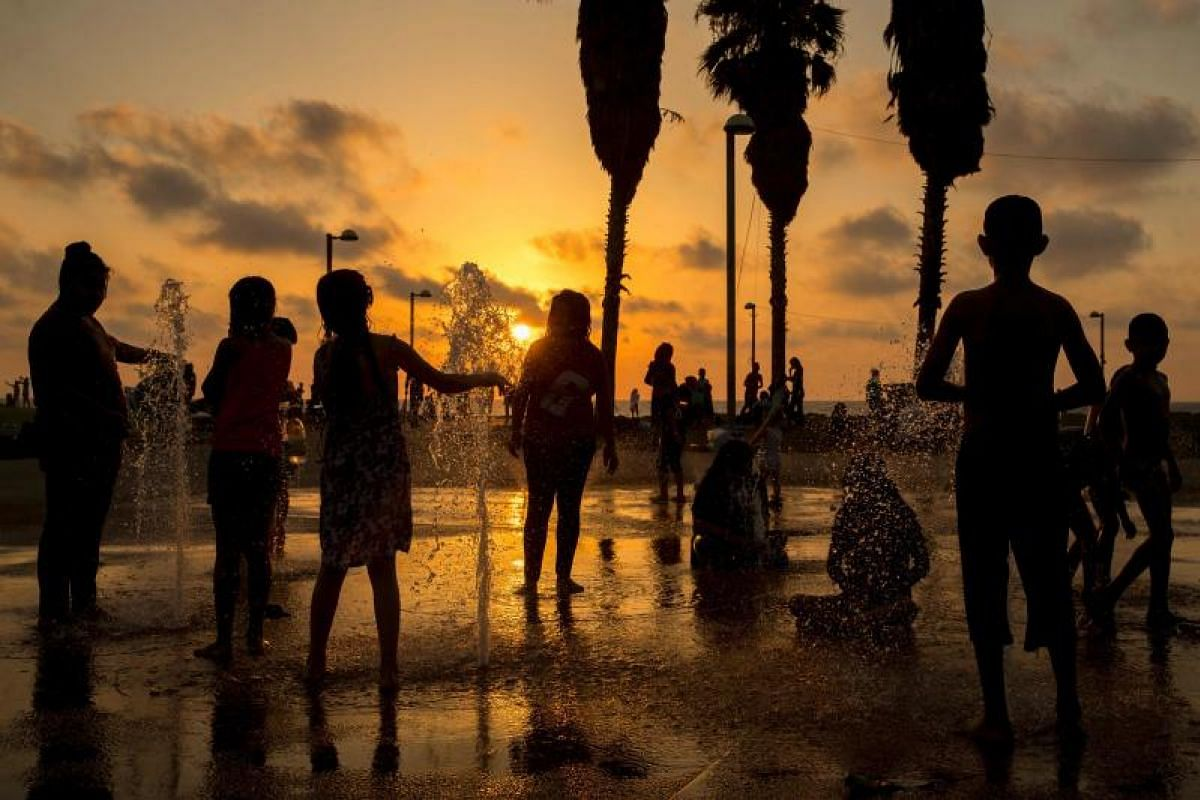 Muslim children playing at a water fountain near a beach on the second day of the Eid al-Fitr holiday in the Israeli Mediterranean coastal city of Tel Aviv on Monday (June 26). The holiday marks the end of the holy fasting month of Ramadan for Muslim